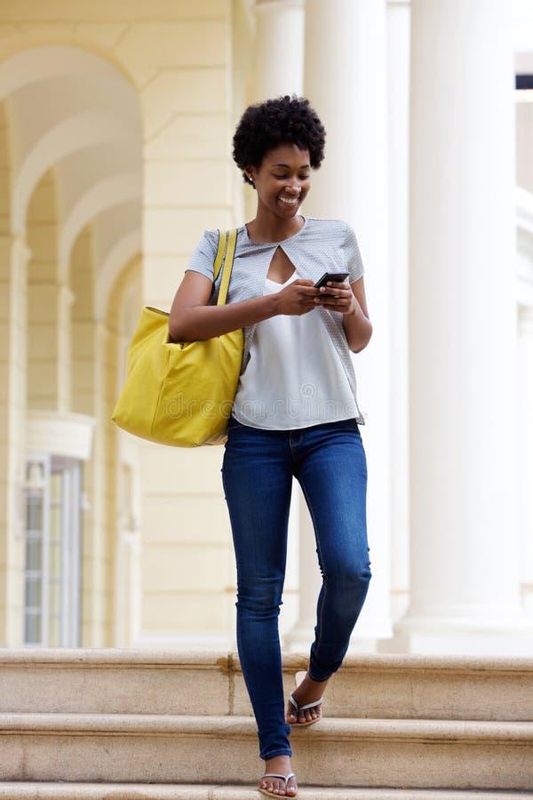 Jonge Afrikaanse vrouw die tekstbericht verzenden royalty-vrije stock foto's