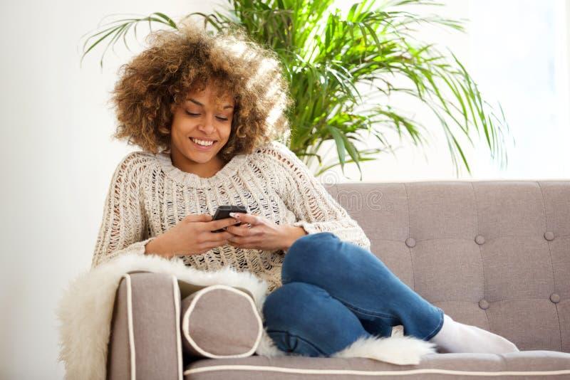 Jonge Afrikaanse vrouw die thuis en mobiele telefoon ontspannen met behulp van royalty-vrije stock afbeeldingen
