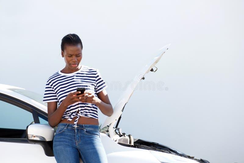 Jonge Afrikaanse vrouw die zich door opgesplitste auto bevinden en mobiele telefoon voor hulp met behulp van stock foto
