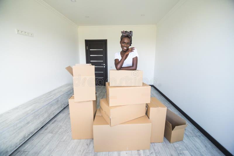 Jonge Afrikaanse vrouw die zich in nieuwe het kartondozen van de flatholding bewegen met bezittingen Bewegend concept stock foto's