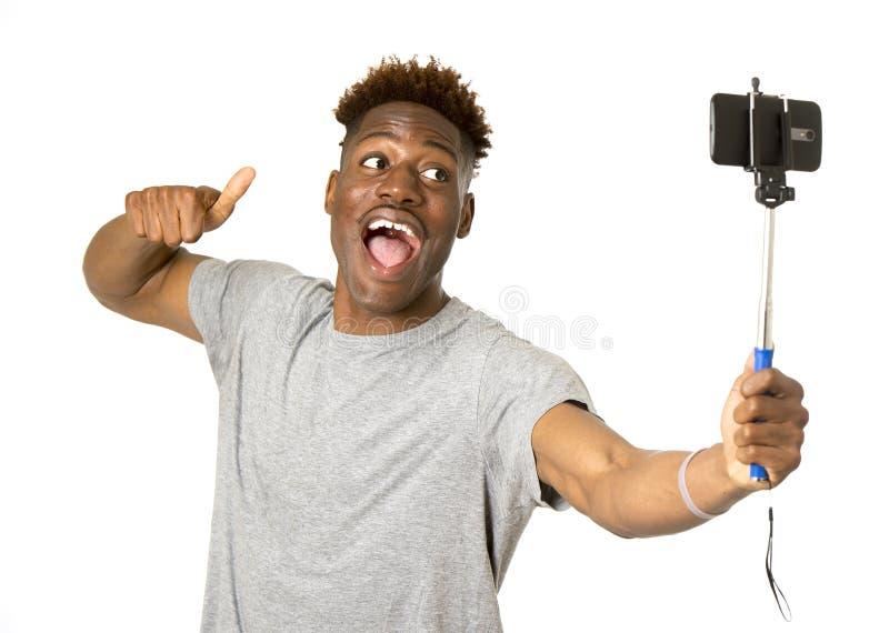 Jonge afro Amerikaanse mens die gelukkig nemend selfie zelfportretbeeld met mobiele telefoon glimlachen stock afbeelding