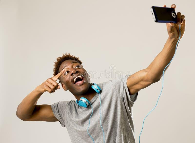 Jonge afro Amerikaanse mens die gelukkig nemend selfie zelfportretbeeld met mobiele telefoon glimlachen royalty-vrije stock afbeelding