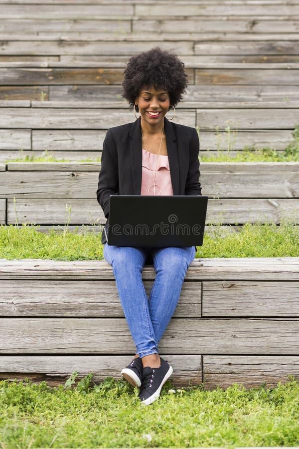 Jonge afro Amerikaanse vrouw die laptop met behulp van Groene achtergronden casua stock afbeeldingen