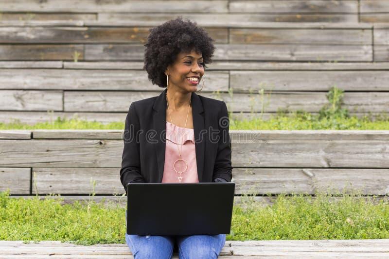 Jonge afro Amerikaanse vrouw die laptop met behulp van Groene achtergronden casua royalty-vrije stock fotografie