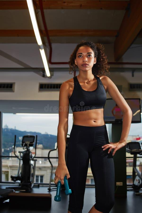 Jonge afro Amerikaanse vrouw die zich met vrije gewichten op geschiktheidscentrum bevinden stock foto's