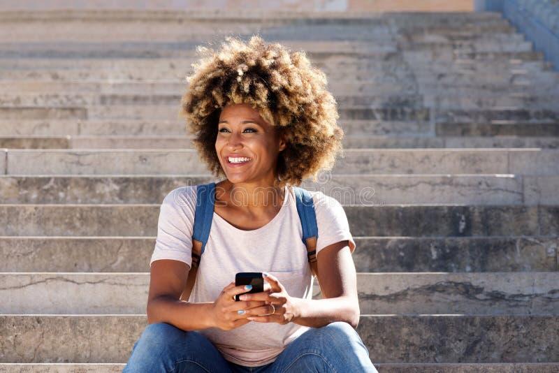 Jonge afro Amerikaanse vrouwelijke zitting op treden met mobiele telefoon en weg het kijken stock fotografie