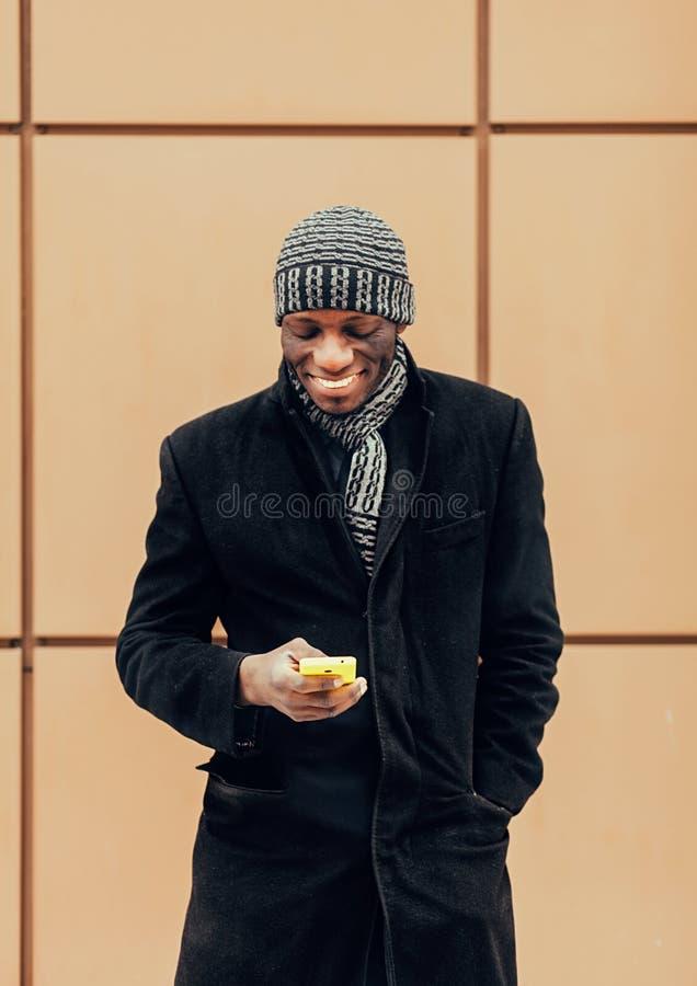 Jonge afro zwarte mens die een slimme telefoon houden royalty-vrije stock afbeelding