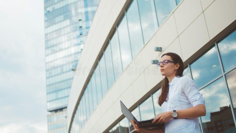 Jonge ambitieuze vrouw met laptop in haar handen op de achtergrond van het commerciële centrum stock afbeelding