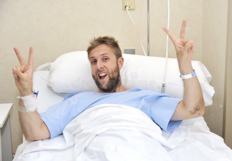 Jonge Amerikaanse mens die in bed bij ziek liggen of zieke het ziekenhuisruimte maar overwinningsteken gelukkig en positief met v stock afbeelding