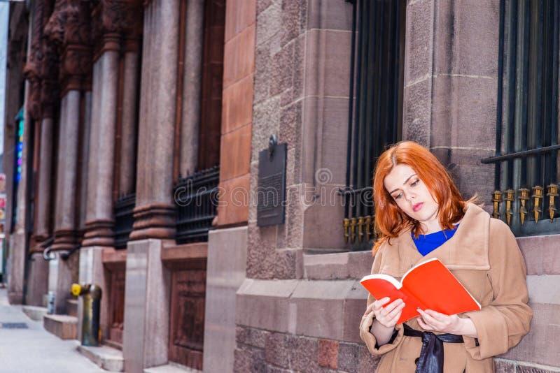 Jonge Amerikaanse Vrouw die rood boek openlucht in New York lezen stock afbeelding