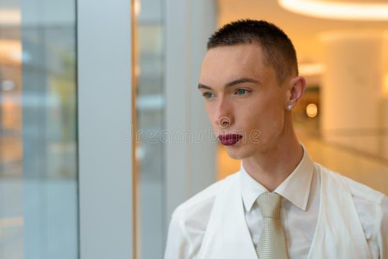 Jonge androgene homoseksuele LGTB-mens die door venster kijken stock fotografie