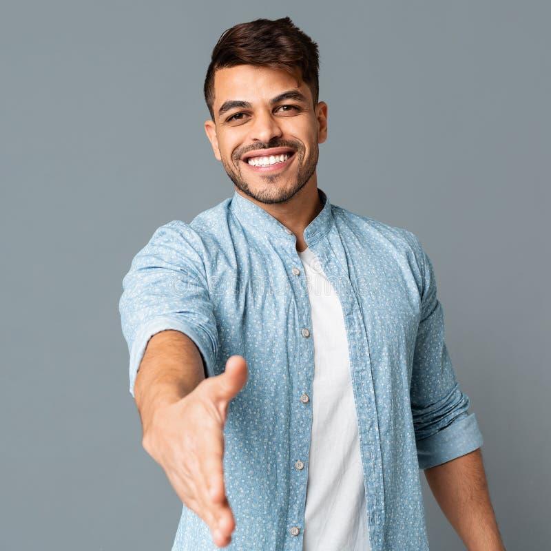 Jonge Arabische Mens die Zijn Hand voor Groet uitrekken stock foto