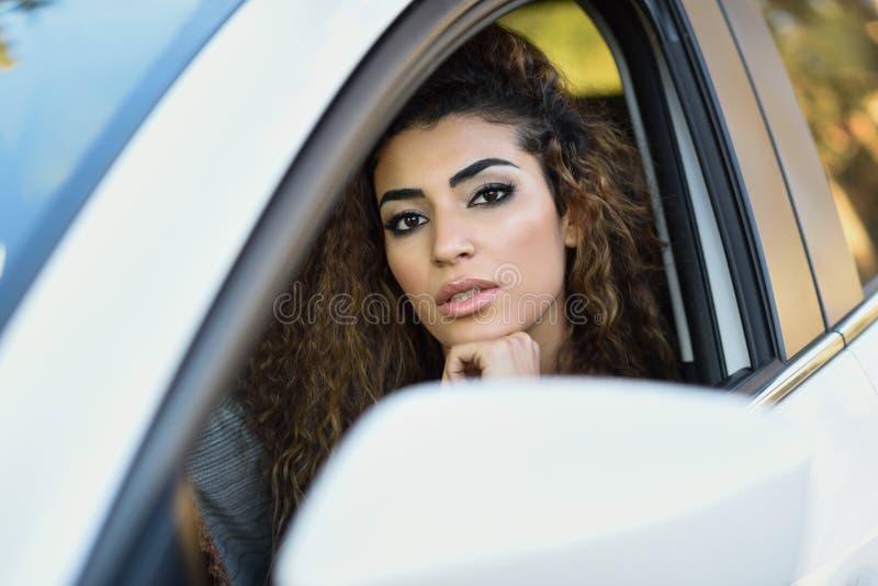 Jonge Arabische vrouw binnen een witte auto die door het venster kijken royalty-vrije stock afbeeldingen