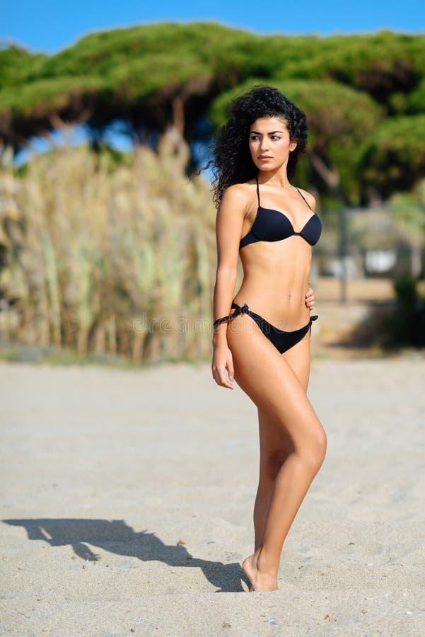 Jonge Arabische vrouw met mooi lichaam in swimwear op een tropisch strand royalty-vrije stock afbeeldingen
