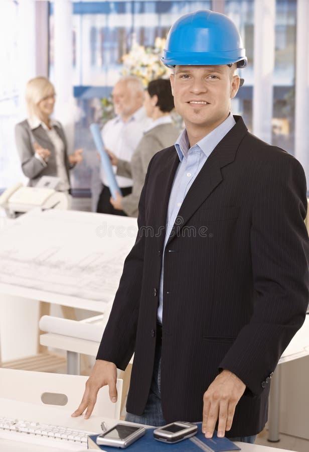 Jonge architect die bouwvakker in bureau draagt royalty-vrije stock fotografie