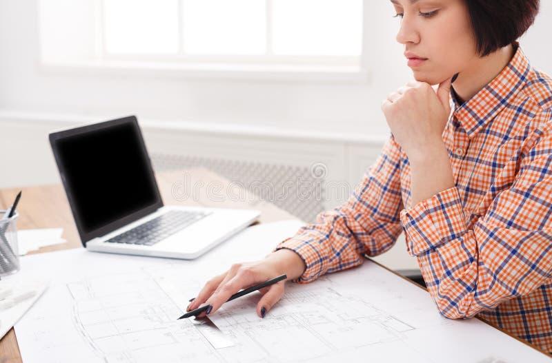 Jonge architect die met blauwdrukken in het bureau werken stock afbeeldingen