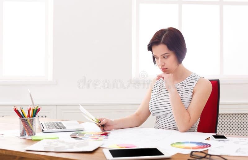 Jonge architect die met blauwdrukken in het bureau werken stock afbeelding