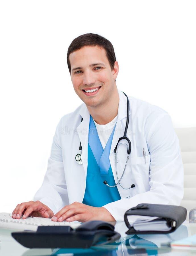 Jonge arts die bij een computer werkt stock fotografie