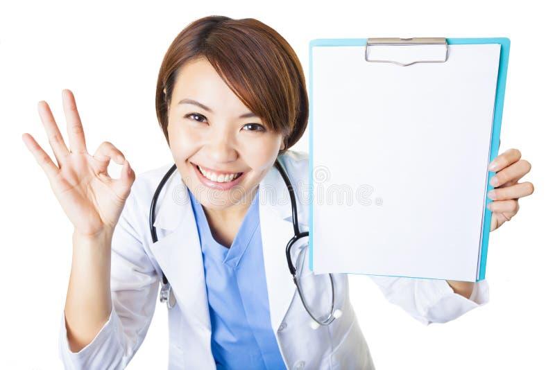 Jonge arts die leeg klembord met o.k. gebaar tonen stock afbeelding