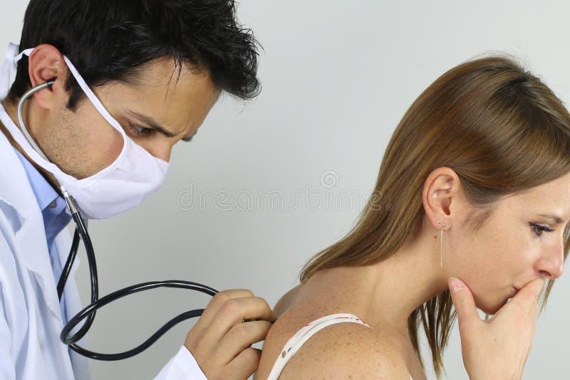 Jonge arts die zijn patiënt onderzoeken stock foto
