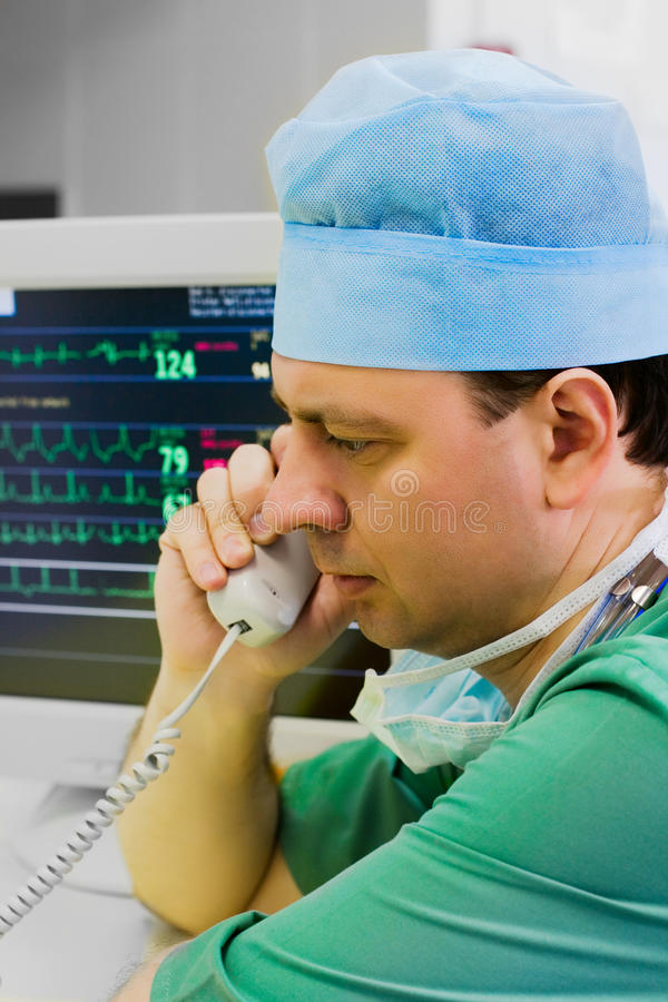 Jonge arts met telefoon in ICU stock fotografie