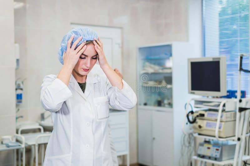 Jonge arts tijdens voorbereiding voor verrichting Medewerker die van chirurg medisch GLB in verrichtingsruimte dragen bij stock fotografie