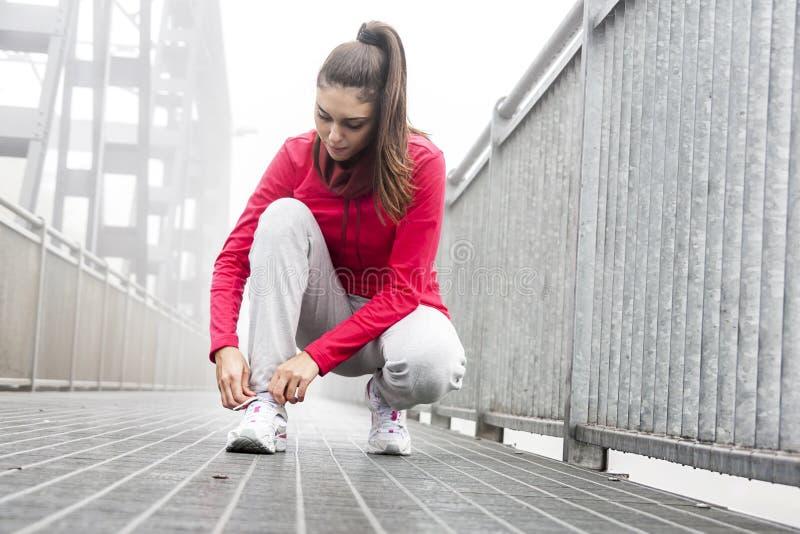 Jonge atleet die zijn schoenen bindt stock foto's