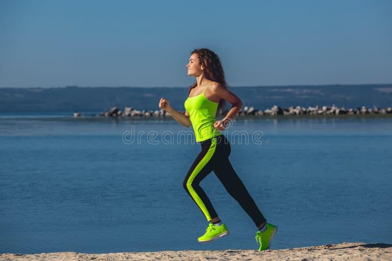 Jonge atleet met krullend haar, lichtgroene bovenkledij en tennisschoenen die op het strand in de zomer, ochtendoefening lopen royalty-vrije stock afbeeldingen