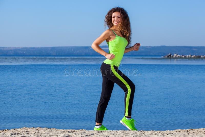 Jonge atleet met krullend haar, lichtgroene bovenkledij en tennisschoenen die op het strand in de zomer, ochtendoefening lopen stock foto's