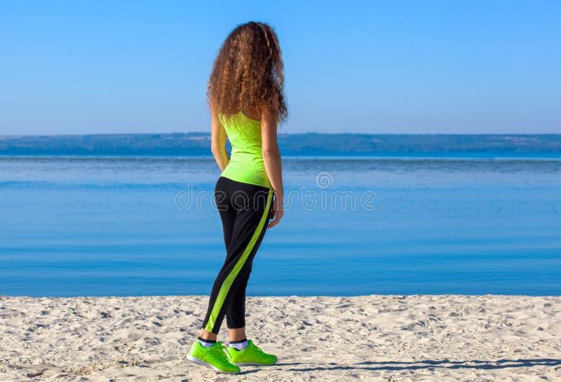 Jonge atleet met krullend haar, lichtgroene bovenkledij en tennisschoenen die op het strand in de zomer, ochtendoefening lopen royalty-vrije stock fotografie