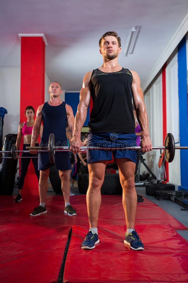 Jonge atleten die barbells op oefeningsmatten opheffen royalty-vrije stock fotografie