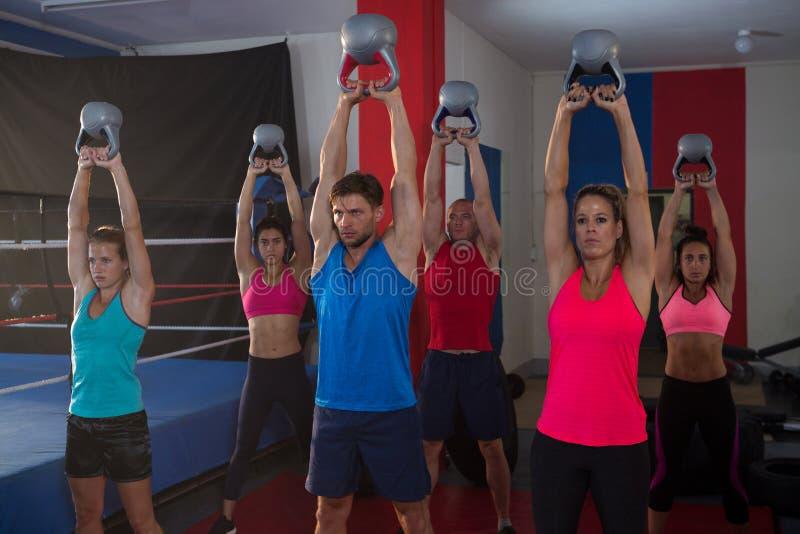 Jonge atleten die ketels opheffen door boksring stock foto