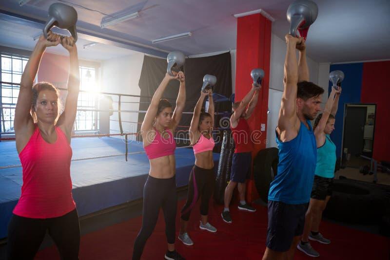 Jonge atleten die ketels opheffen tegen boksring stock foto