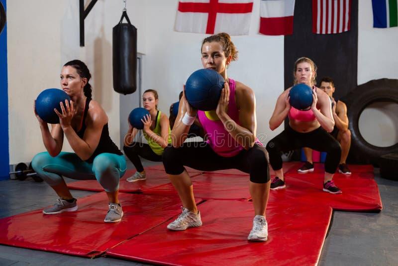 Jonge atleten die met oefeningsballen buigen op matten stock afbeelding