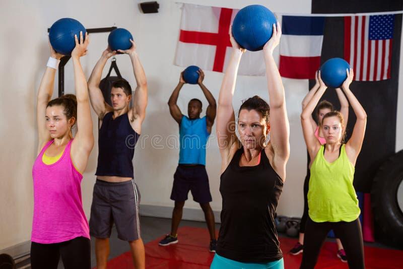 Jonge atleten die oefeningsballen met opgeheven wapens houden stock fotografie