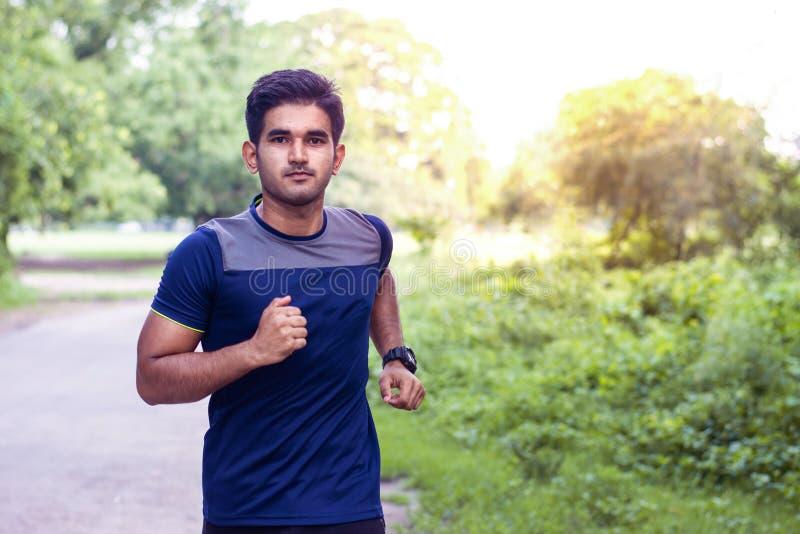 Jonge atletenmens die in sportengrond loopt op weg in sportenslijtage stock foto's