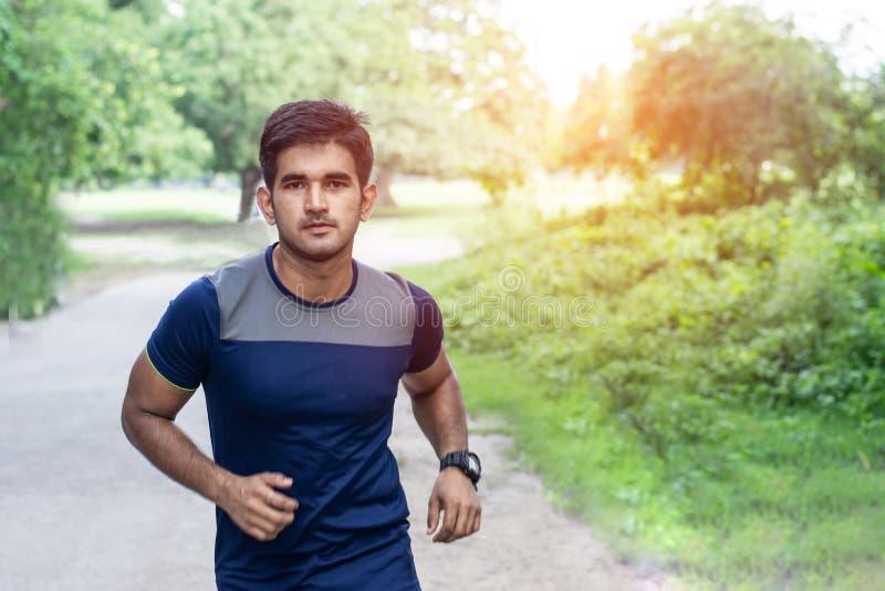 Jonge atletenmens die in sportengrond lopen op weg in sportenslijtage royalty-vrije stock afbeeldingen