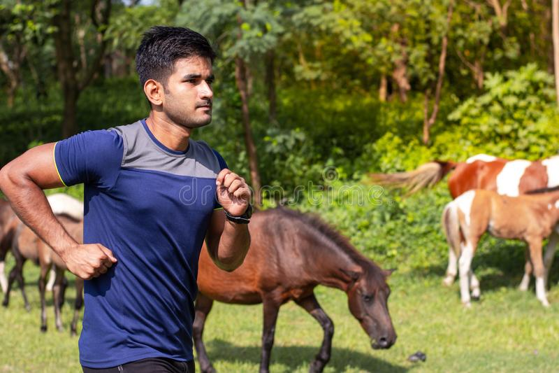 Jonge atletenmens die in sportengrond lopen op weg in sportenslijtage royalty-vrije stock fotografie