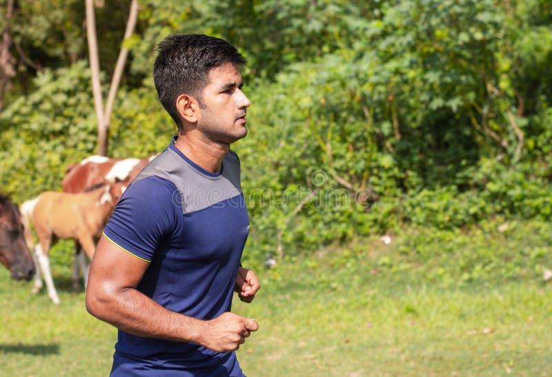 Jonge atletenmens die in sportengrond lopen op weg in sportenslijtage royalty-vrije stock foto