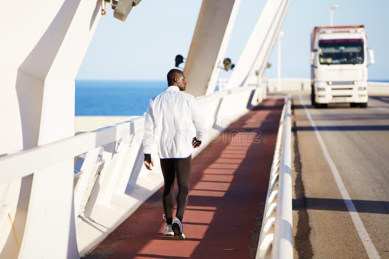 Jonge atletische Afro-Amerikaan gaat na jogging op de brug stock afbeelding