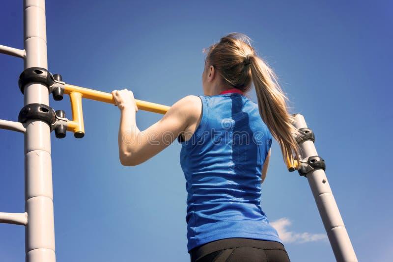 Jonge atletische geschiktheidsvrouw die bij openluchtgymnastiek uitwerken die trekkracht UPS doen bij zonsopgang stock afbeelding