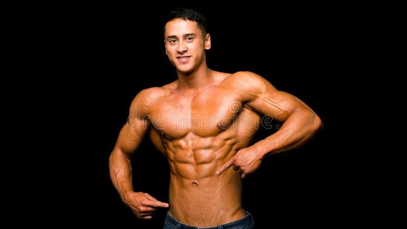 Jonge atletische mens die door vinger zijn perfecte abs over donkere achtergrond tonen royalty-vrije stock afbeelding