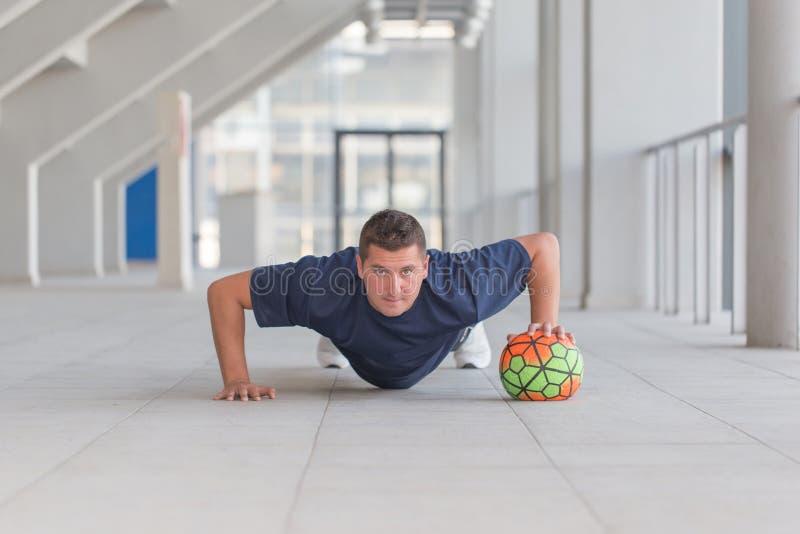 Jonge atletische mens die duw UPS met voetbalbal doen royalty-vrije stock afbeelding