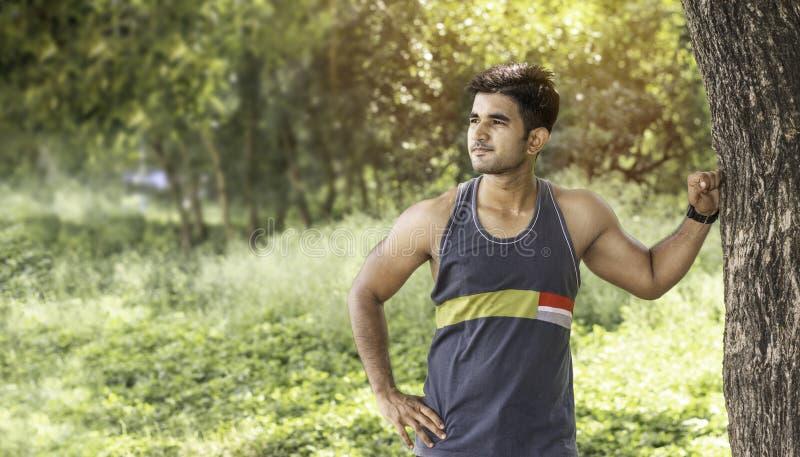 Jonge atletische mens die een onderbreking nemen onder boom tijdens een opwindende jogging openlucht stock afbeelding