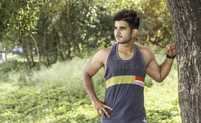 Jonge atletische mens die een onderbreking nemen onder boom tijdens een opwindende jogging openlucht stock foto's