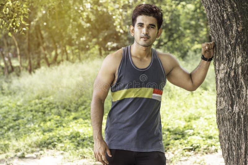 Jonge atletische mens die een onderbreking nemen onder boom tijdens een opwindende jogging openlucht stock afbeeldingen