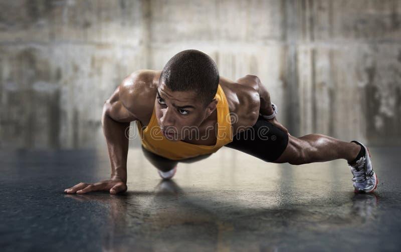 Jonge atletische mens die opdrukoefeningen doen stock fotografie