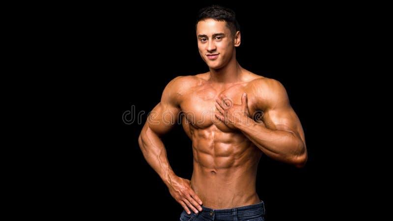 Jonge atletische mens met perfecte abs over donkere achtergrond royalty-vrije stock foto's