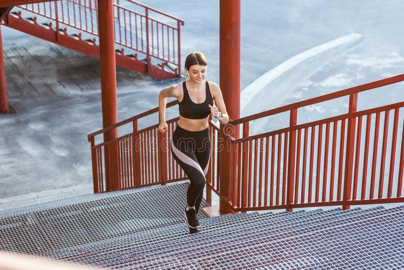 Jonge atletische slanke mooie vrouw het lanceren treden die cardiointerval opleiding in zwarte modieuze sportwear in de straat do stock foto
