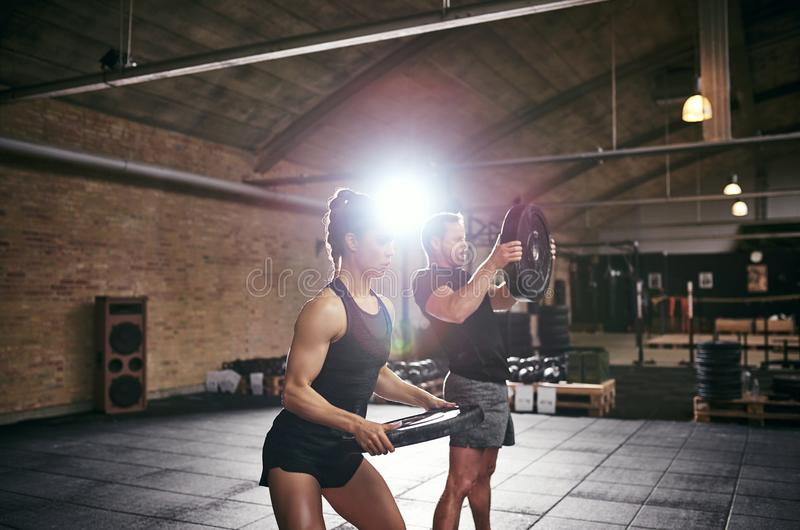 Jonge atletische sportspeople het opheffen gewichten in gymnastiek stock afbeeldingen